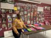 Photo of Sharon Curry in the Community Center. Pictures of inspirational people cover the walls and her student's notebooks fill the table. Happy Holidays.
