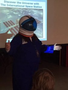 Pat in her spacesuit while giving a presentation